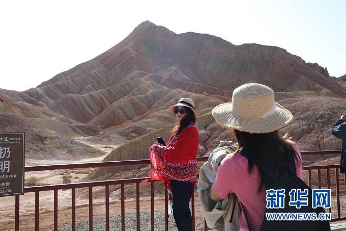 游客在张掖七彩丹霞景区拍照留念 新华社记者 李杰 摄