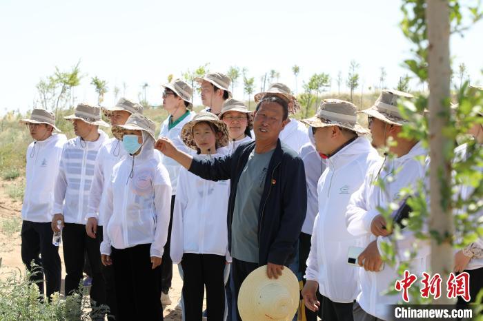 """图为第二代治沙人石银山带领志愿者重走三代人的治沙路。 """"绿动未来""""供图"""
