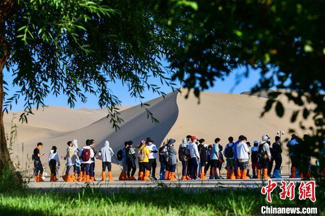 6月上旬,游人在绿树成荫的鸣沙山月牙泉景区观光游览。 王斌银 摄
