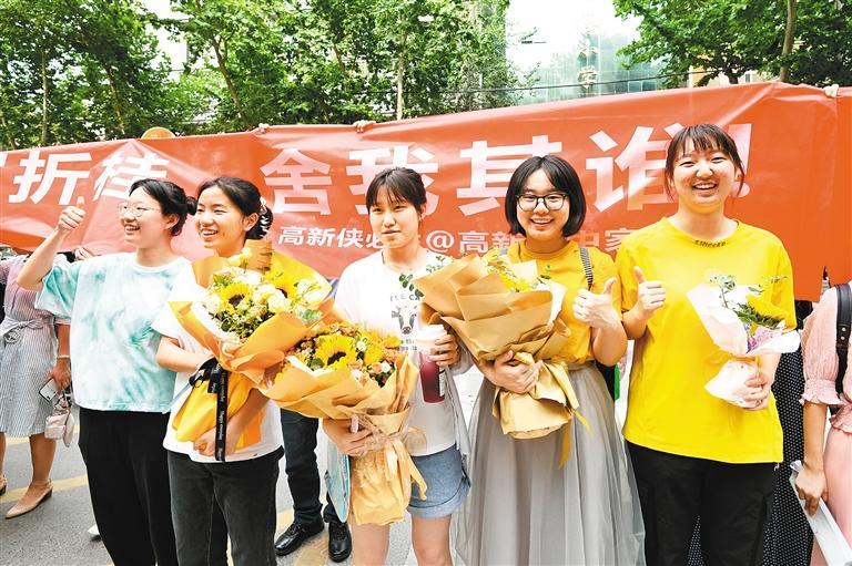 6月8日下午,在西安市第八十五中学考点,考生们手捧鲜花,合影留念。