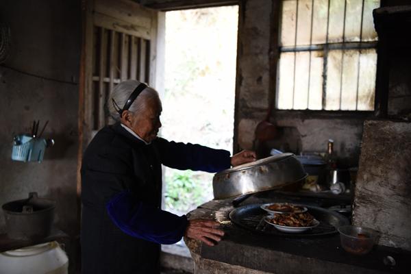张荷仙老人给自己做早饭,把昨日所做菜品放入灶中加热。