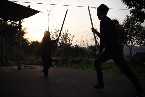张荷仙老人与儿子进行棍法练习。