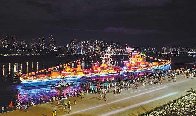 """六月三十日晚,九龙坡建设码头,166舰灯光秀吸引了许多市民驻足欣赏。当晚,166舰""""庆祝建党百年主题灯光秀""""正式开启。 郑宇 摄"""