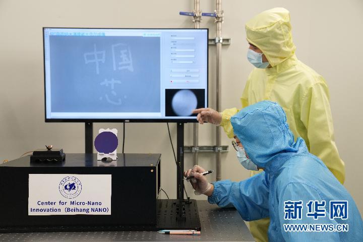 """6月24日,在北京航空航天大学,集成电路学院科研人员(前)在5个原子层厚的纳米磁性薄膜上写下""""中国芯""""。新华社记者鞠焕宗摄"""