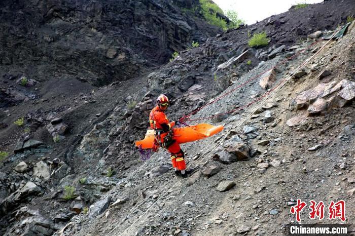 """消防指战员在""""泥石流埋压""""科目中进行空中绳索被困人员营救操作。 曹继川 摄"""