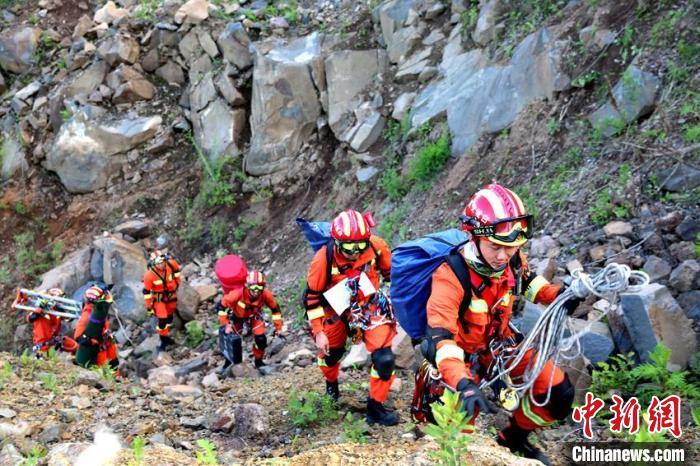 """参演消防指战员向""""陡坡攀岩救援""""科目实施地点进发。 曹继川 摄"""