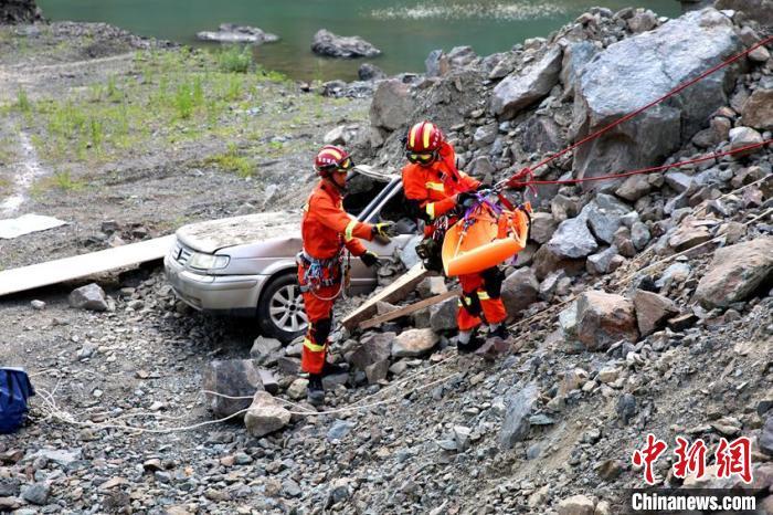 """消防指战员在""""泥石流埋压""""科目中对埋压车辆中被困人员进行营救。 曹继川 摄"""