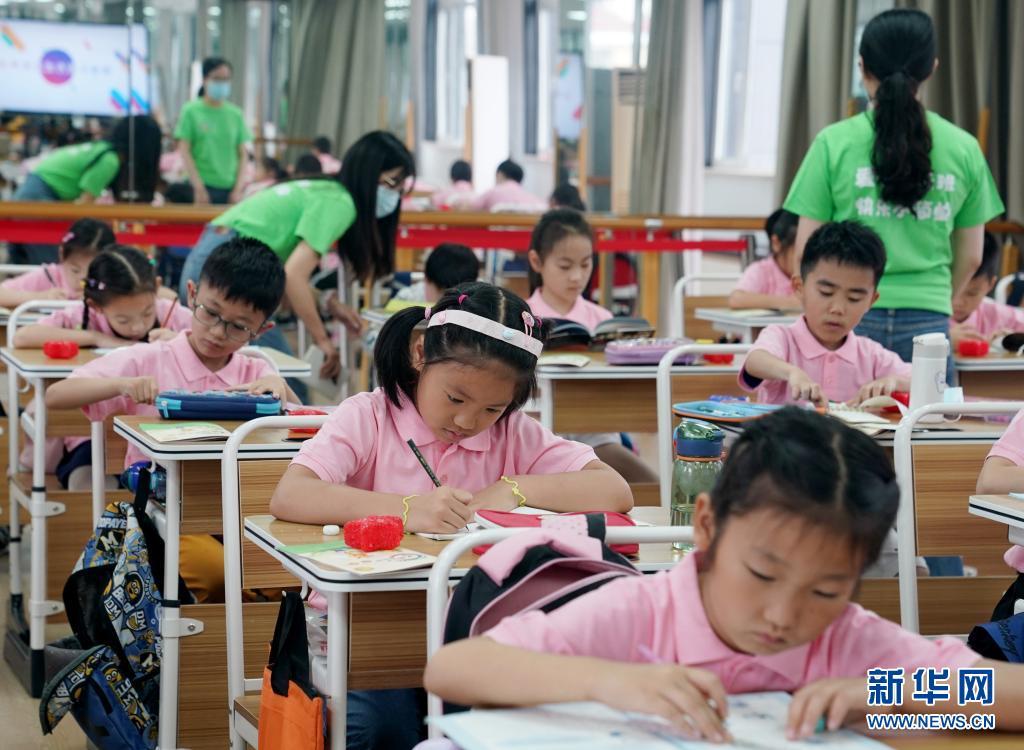 7月5日,上海市爱心暑托班小学生在志愿者辅导下写作业。新华社记者 刘颖 摄