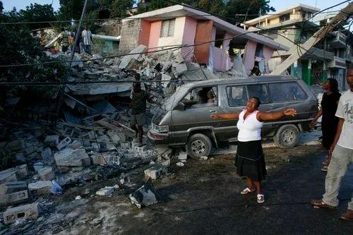 2010年1月13日,在发生地震的海地首都太子港,一名女子在被震毁的房屋旁哭泣。新华社/路透