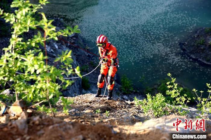 """参演消防指战员在""""人员跌落斜坡救援""""科目中进行悬崖下降。 曹继川 摄"""