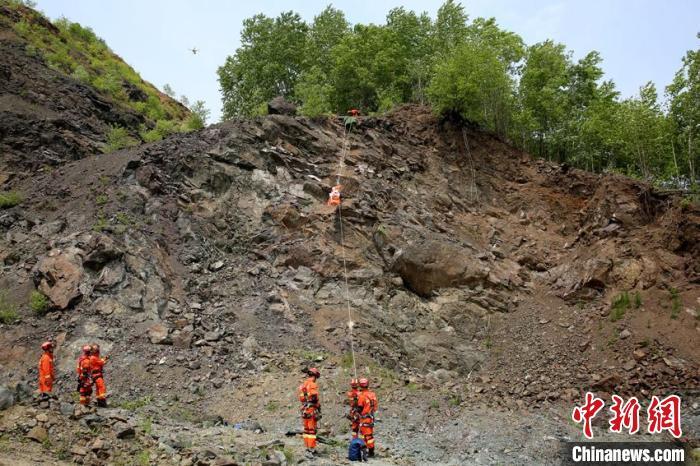 """参演消防指战员在""""陡坡攀岩救援""""科目中开展被困人员安全转运。 曹继川 摄"""