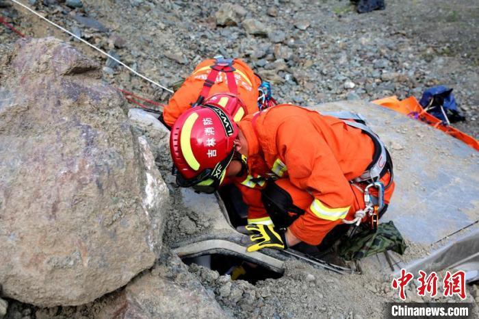 """消防指战员在""""泥石流埋压""""科目中对埋压车辆中的被困人员进行营救。 曹继川 摄"""