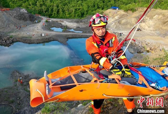 """消防指战员在""""人员跌落斜坡救援""""科目中利用消防救援多功能担架对崖下被困人员进行空中绳索营救。 曹继川 摄"""