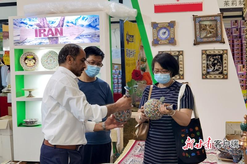 伊朗客商穆学龙(左)在兰洽会上向消费者介绍伊朗特色商品 新甘肃·甘肃日报记者 刘健 摄