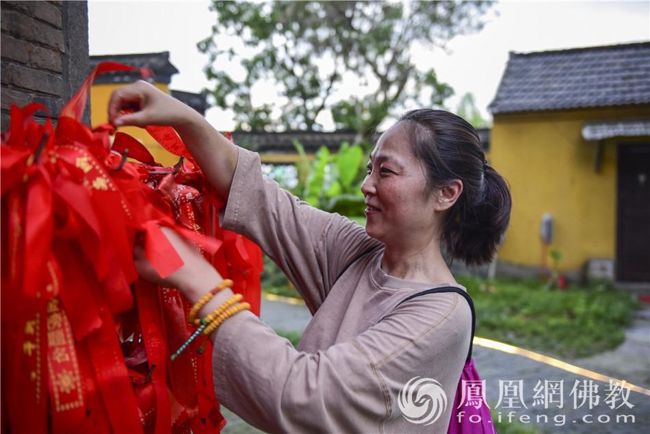 考生家长在文峰塔前悬挂还愿祈福带(图片来源:凤凰网佛教 摄影:季利)
