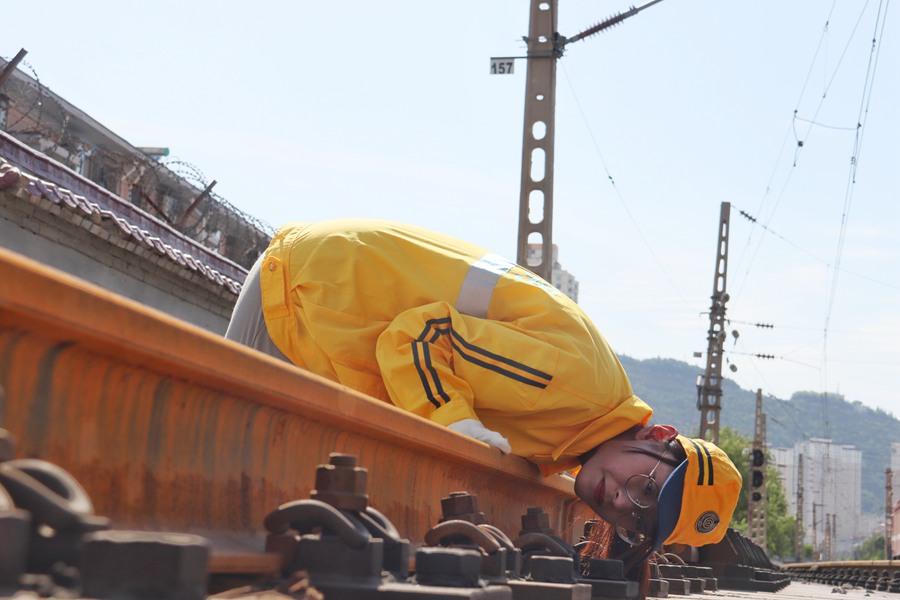 工作人员趴在钢轨上,查看钢轨是否平顺。(王光辉 摄)