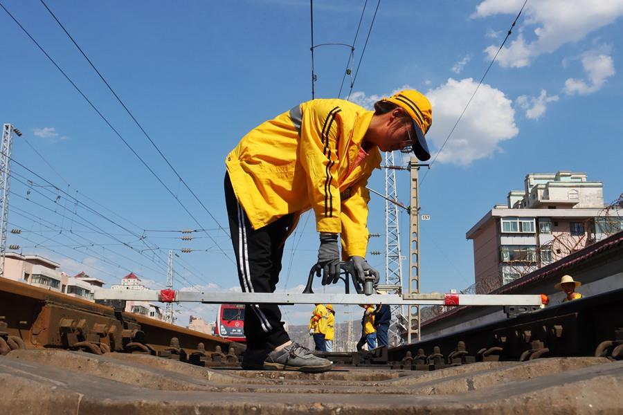工作人员用长道尺标注轨距 (王光辉 摄)