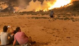 (在靠近山火的地区,居民们逃出家门,坐在海滩边,看着近在咫尺的山火。图源益美传媒)