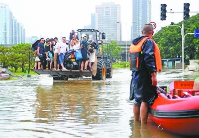 郑州市金水东路,城市志愿者用铲车摆渡转移群众。记者刘斌 摄