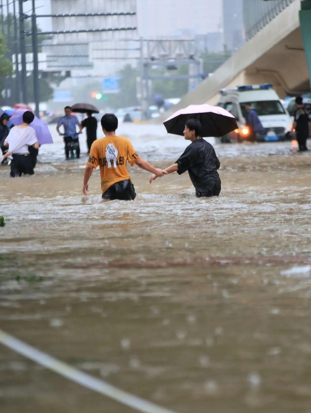 ▲ 7月20日,市民走在齐腰深的积水里。图/视觉中国