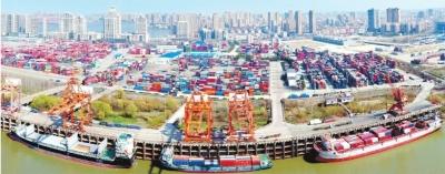 阳逻港一期码头一片繁忙,三艘货轮正停靠在码头上货、卸货,龙门吊、卡车司机配合精准到位,车辆出入有序。