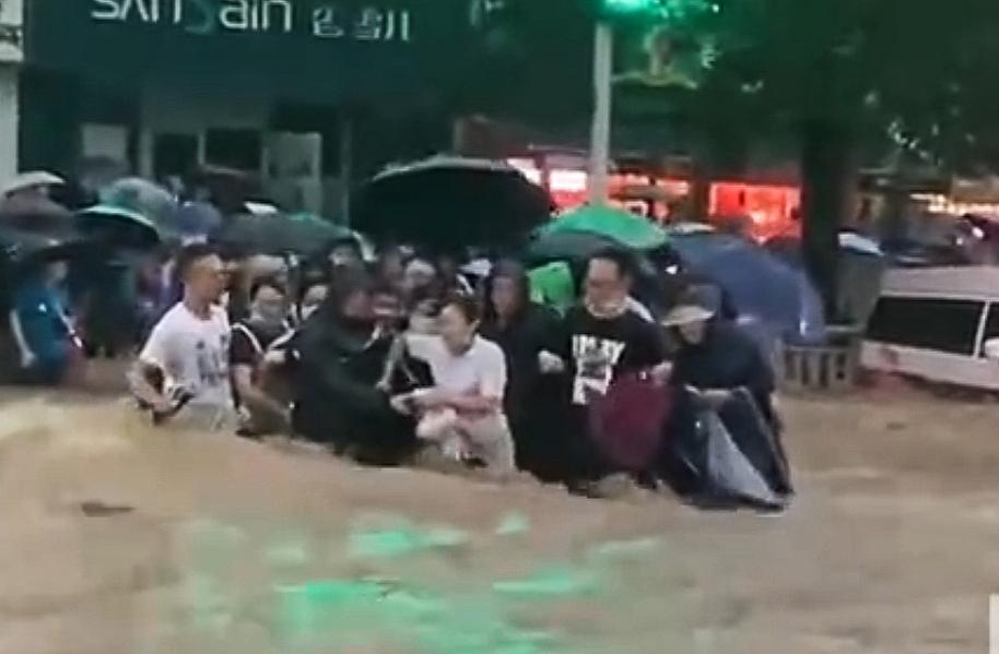 (郑州市民在暴雨中相互扶持涉水行走。图源正观新闻)