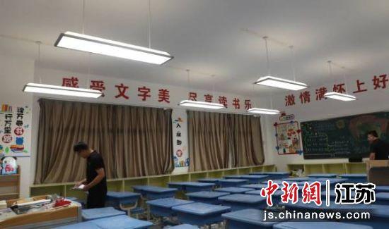 施工人员将教室内的灯具更换为节能护眼灯。谷京 摄