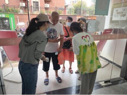 志愿者为居民扫码、测体温