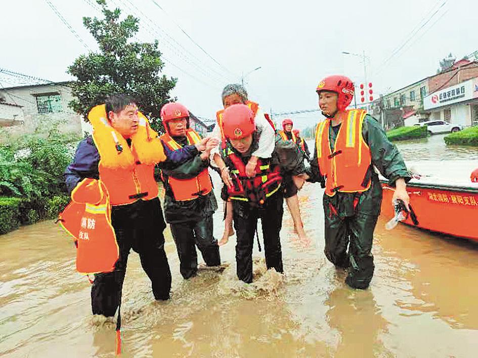 我省消防指战员在河南省长葛市王皮庙村转移受困群众。(通讯员 张旭 摄)