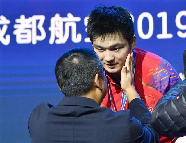 刘国梁拍脸鼓励樊振东。