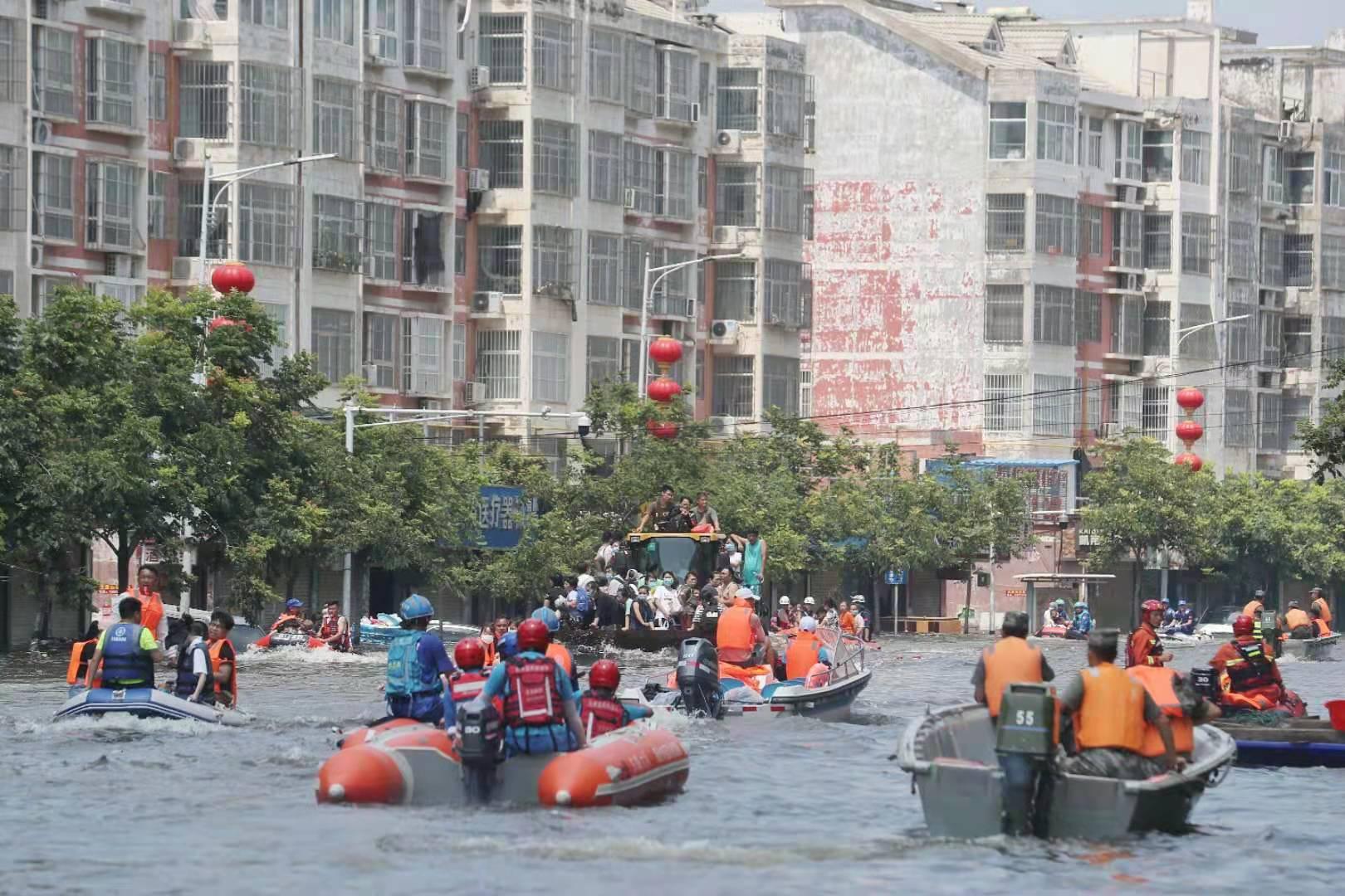 26日下午,医院门口的学院西路上,铲车、冲锋舟在转运人员。新京报记者 王飞 摄