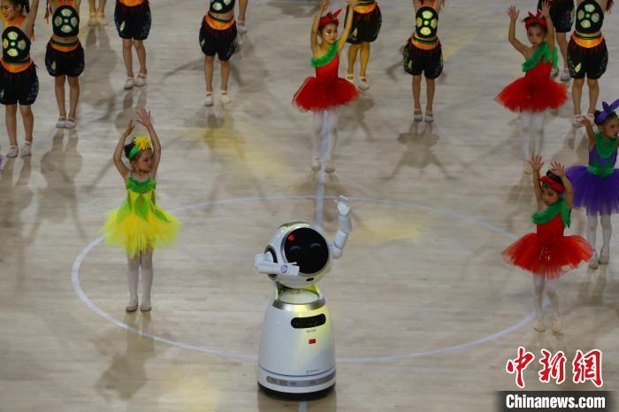 图为开幕式上,青少年与机器人共舞。 刘占昆 摄