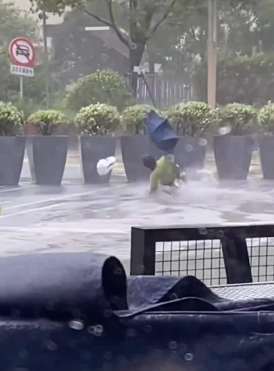 """台风""""烟花""""袭击上海 女子大街上被吹跑"""
