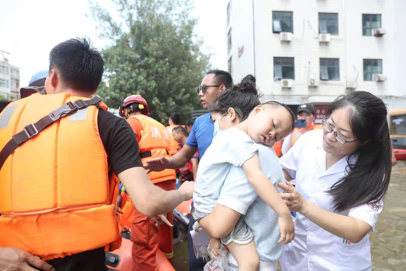 26日下午,新乡医学院第一附属医院住院楼门口,等待转运的孩子趴在妈妈肩膀上。