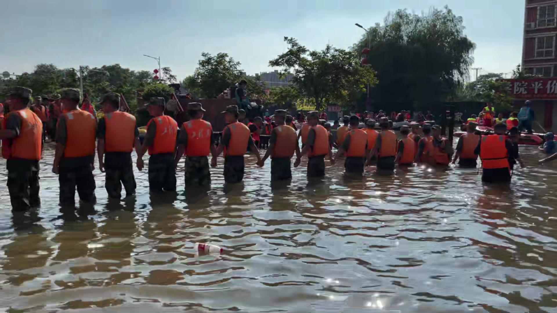 26日下午4时左右,第83集团军某工程防化旅组成人墙协助转运病人。新京报记者 王瑞文 摄