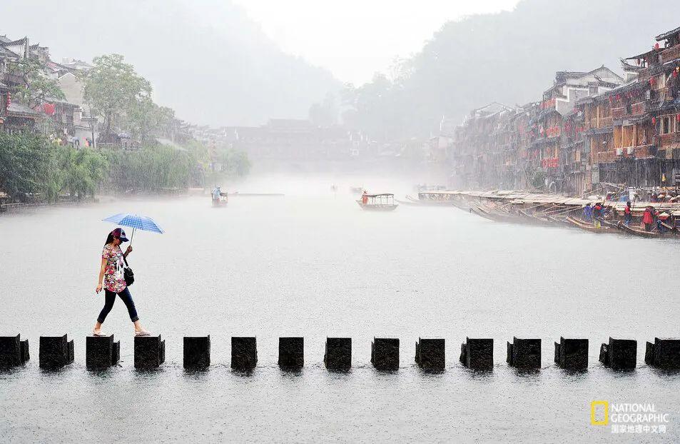 一名女子撑着雨伞,从中国凤凰古城的跳岩桥上走过。 图源:XINHUA/REDUX