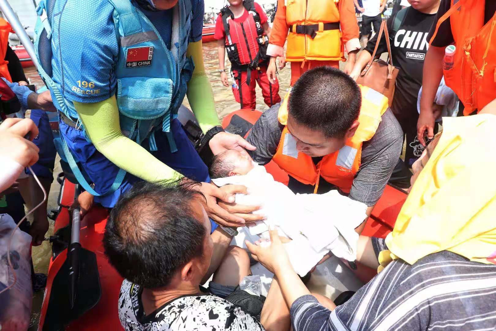 26日下午1点左右,潘勇一家被转运,救援人员正小心翼翼托举着刚出生7天的婴儿。