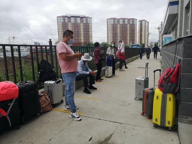 8月1日,乘客们携带行李在核酸检测点外休息。摄影/章轲