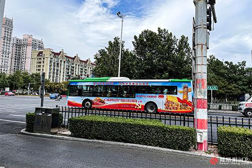"""以红色为主基调,贴有""""庆祝中国共产党成立100周年""""的公交车亮相街头,成为街头一道独特风景线。"""