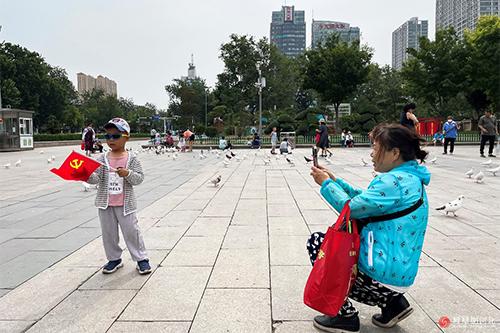 在广场上,小朋友挥舞着党旗,家人拍照留念。