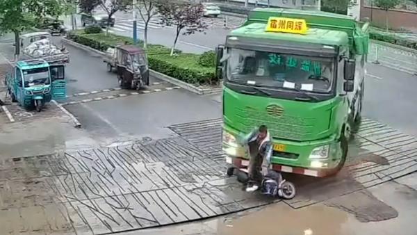 电动车被重型自卸货车撞倒 连人带车卷入车底