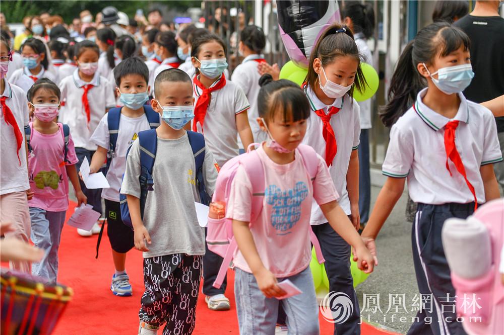 新入学的一年级同学在高年级同学的陪同下进入学校。梁琪佳摄