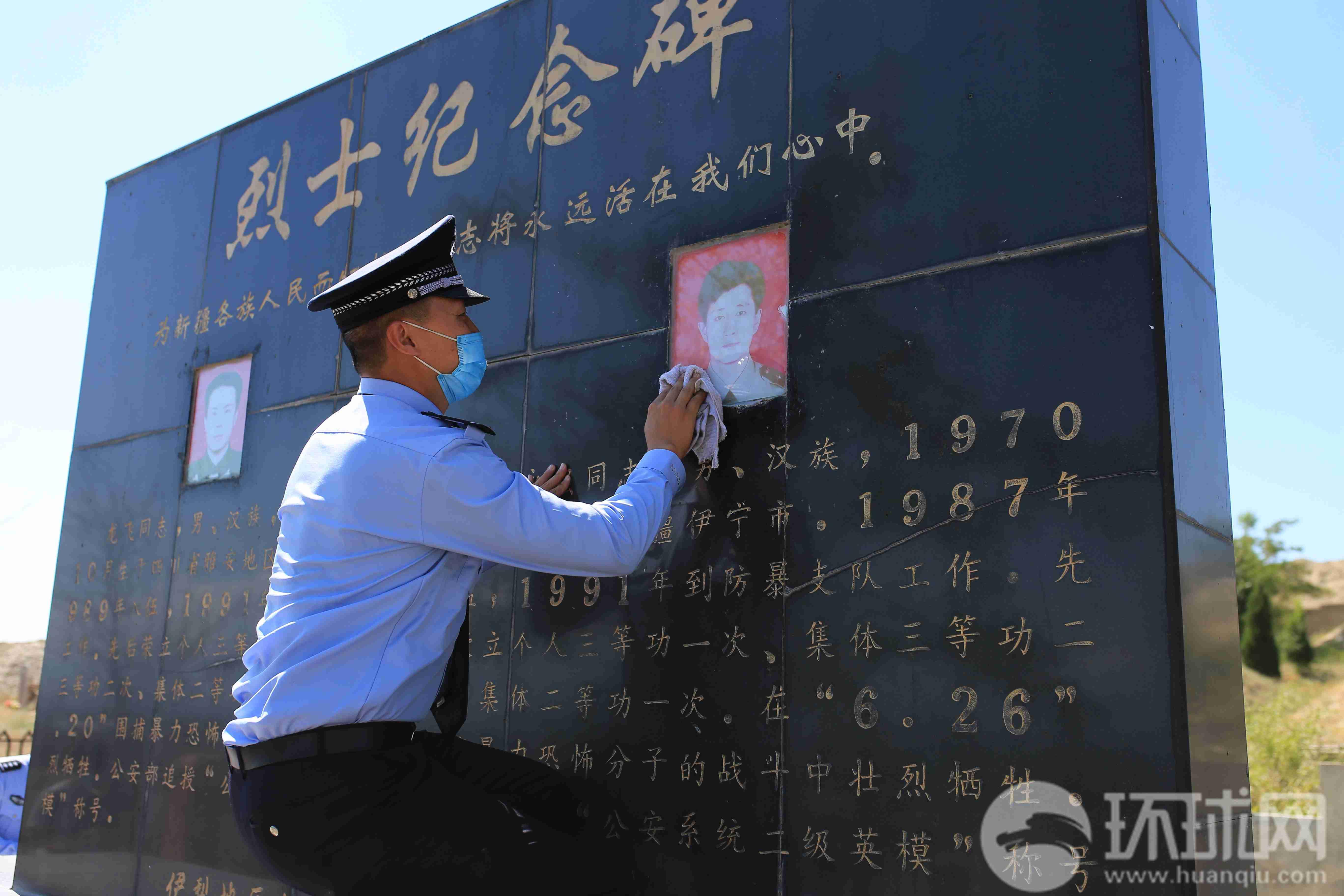 伊犁州公安局的干警在擦拭龙飞和孔永强烈士的纪念碑。摄影 范凌志