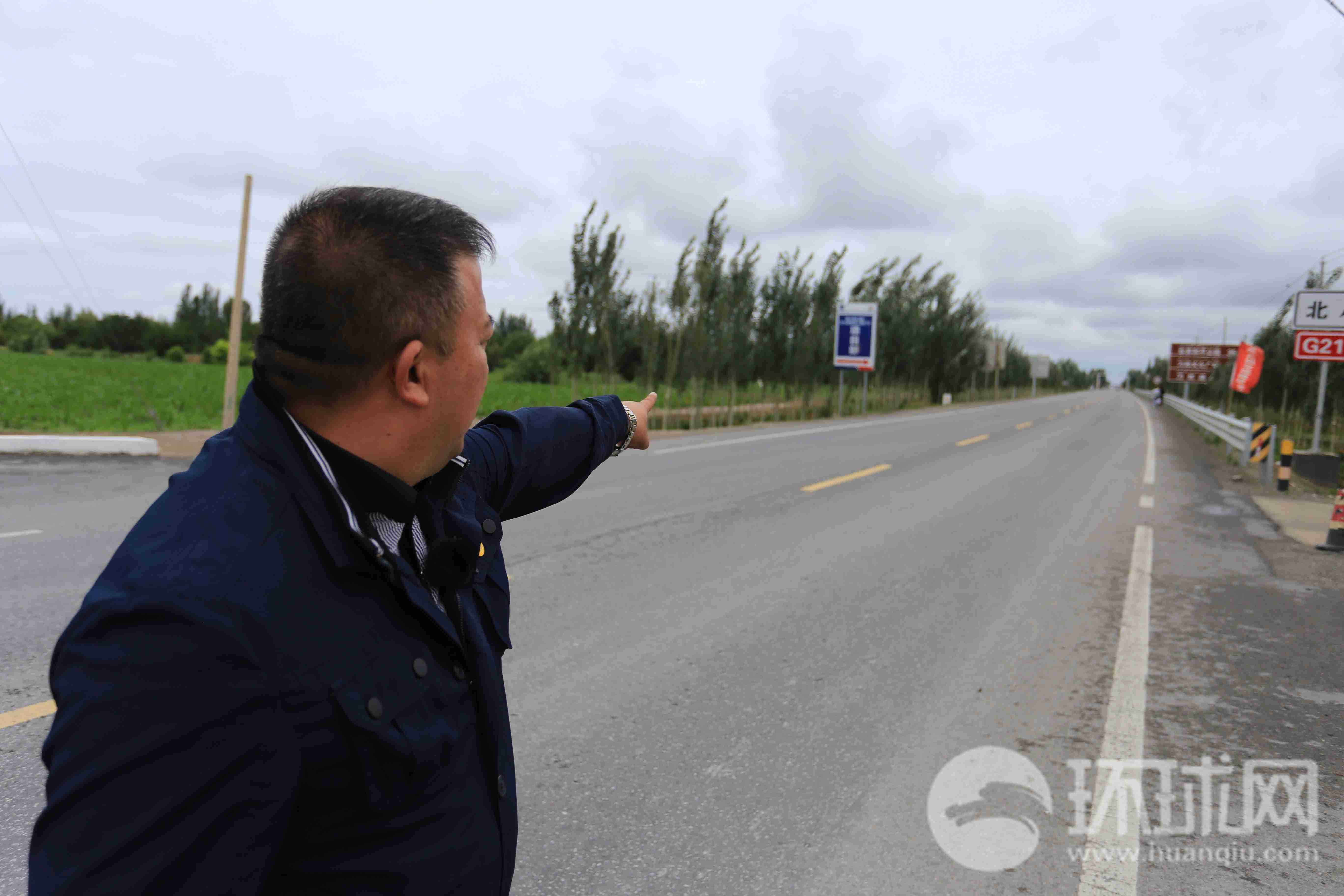 努尔麦麦提手指的方向,就是当年暴徒跟公安干警对峙的地方。摄影 范凌志