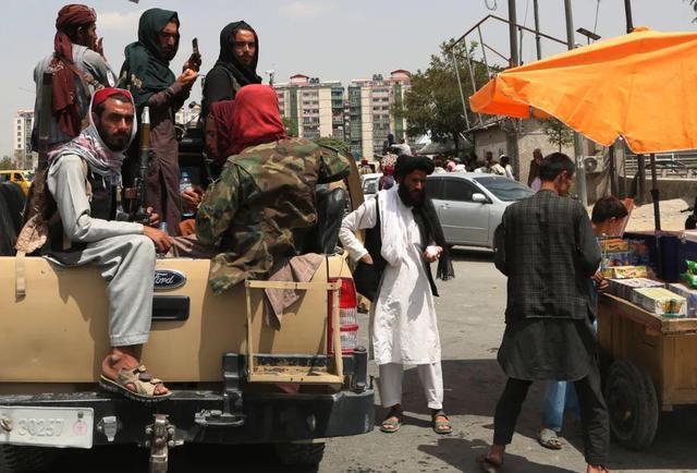8月17日,阿富汗塔利班成员在喀布尔街头向小贩购物。图自新华社