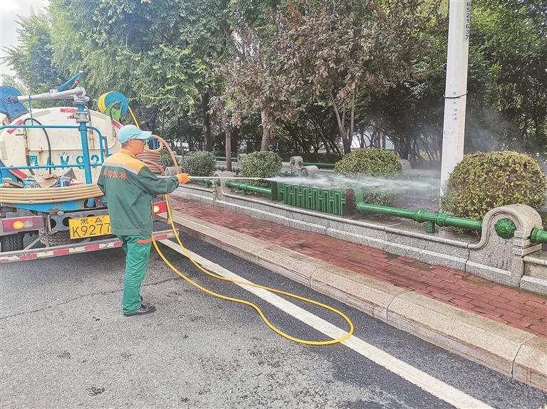 工作人员对出城口绿化树木进行养护。