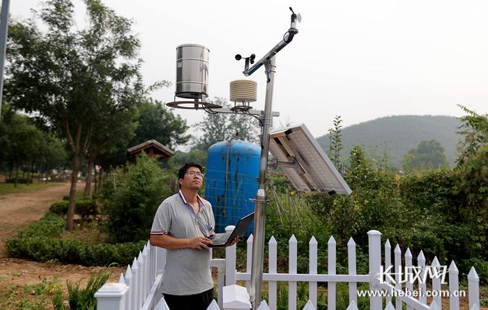 技术人员冯会斌在太阳能智能气象站检查设备的工作情况。该设备具备7种气象数据监测功能,所有数据都会实时回传,形成大数据进行综合分析。王爽 摄