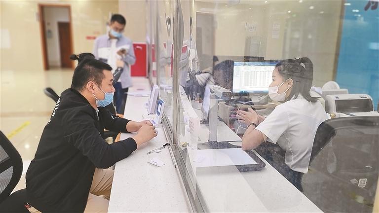 办事群众在窗口前咨询并办理医保业务。