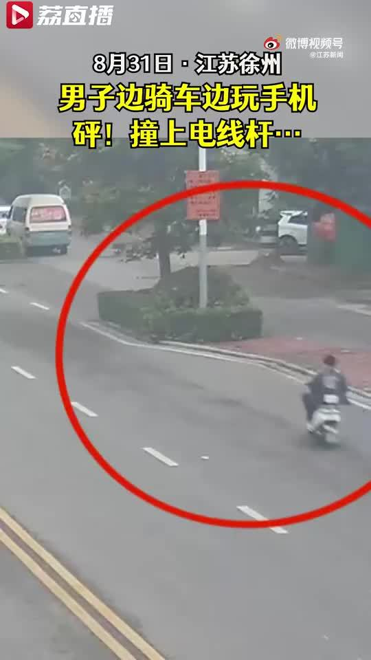 男子骑车玩手机撞上电线杆