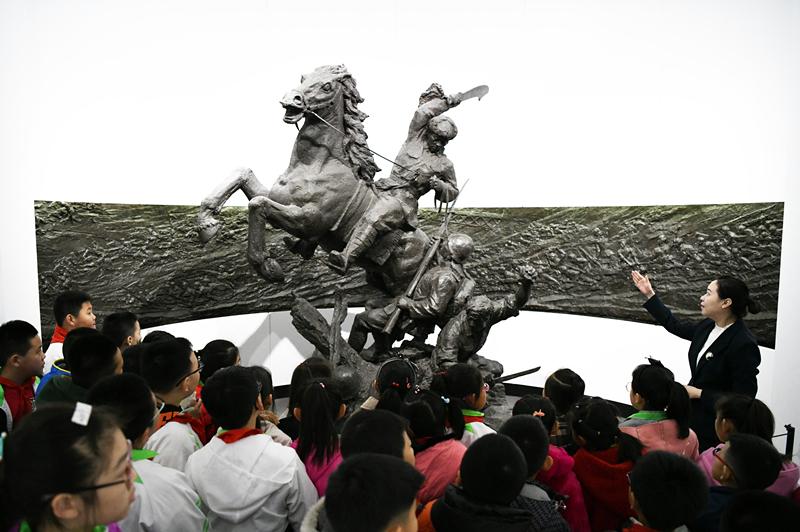 2019年4月4日,在东北烈士纪念馆,学生们在听讲解员讲解。